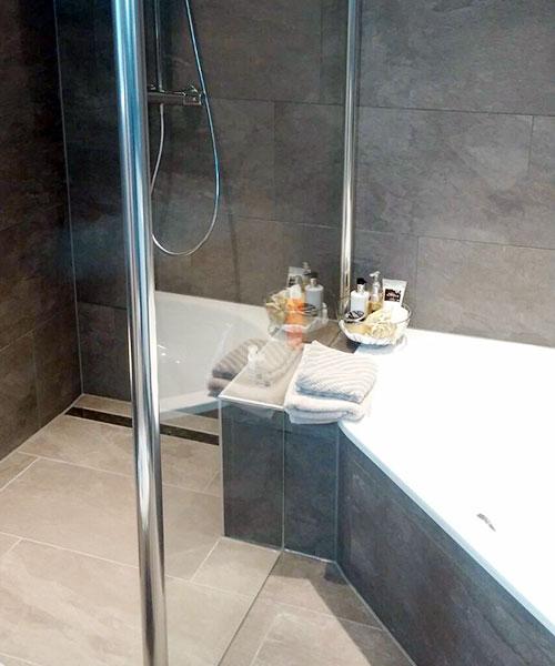 Sonderlösung: Dusch-/Badewannenabtrennung aus Glas mit gefliester Ablagemöglichkeit