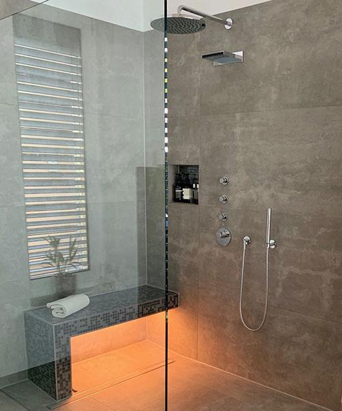 Dusche mit Linienentwässerung, befliester und beleuchteter Sitzbank und integrierter Wandnische