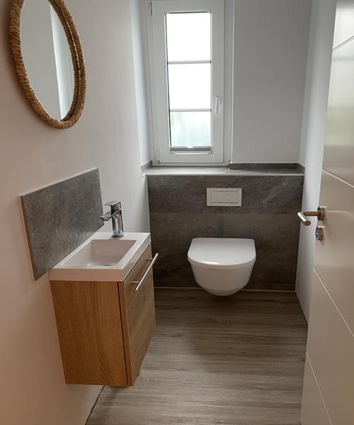 Feinsteinzeug Format 30 x 60 cm belebte Quarzitoptik grau multicolor matt an der Vorwandinstallation und als Spritzschutz hinter dem Waschbecken.